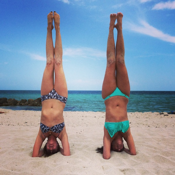 Practicing headstands on South Beach with Betsy (left)